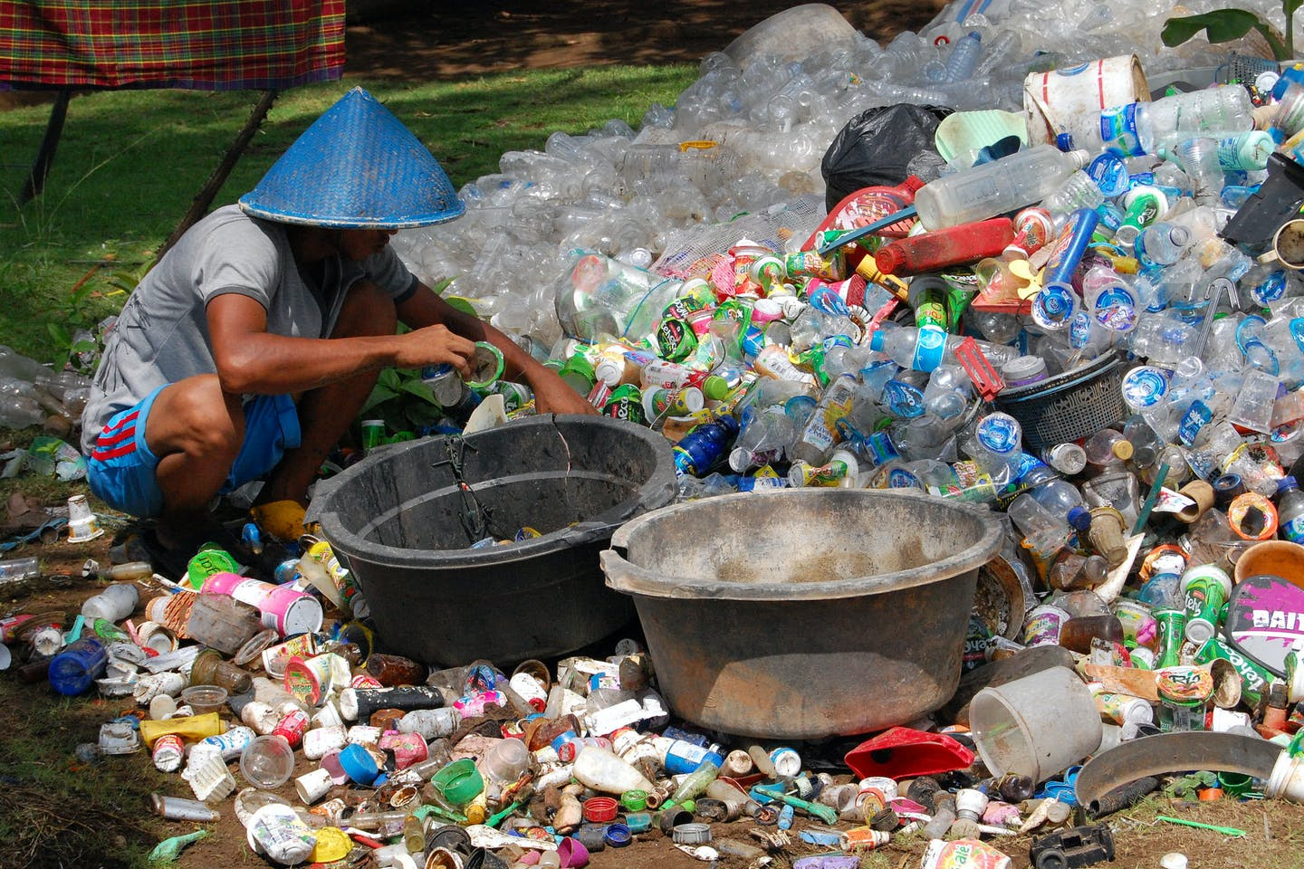 A collector sifts through plastic waste in Indonesia