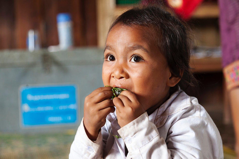 child eats in Laos