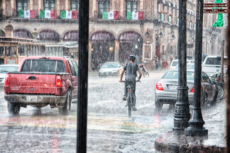 boy riding bike in the rain
