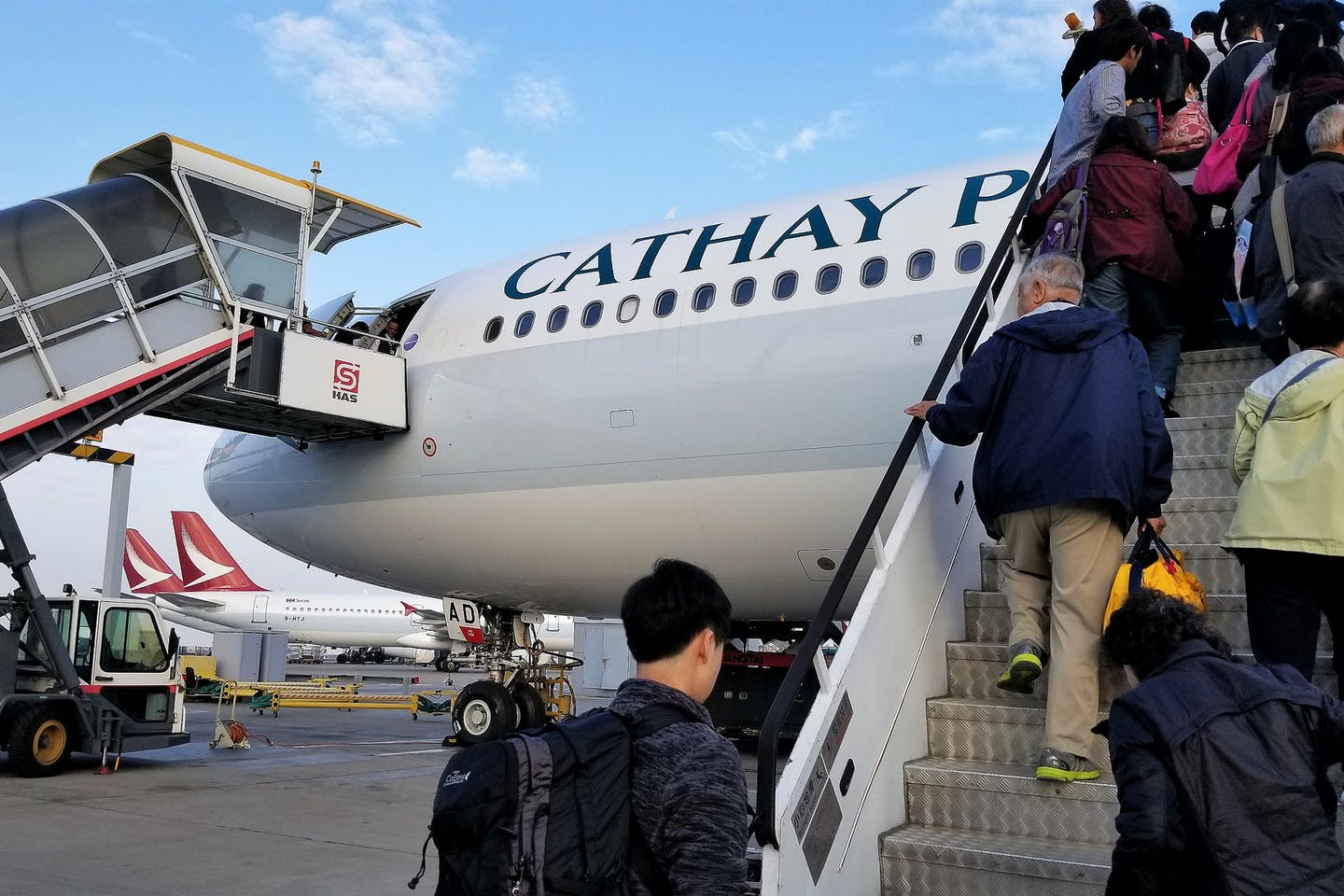 Travellers board a Cathay Pacific flight