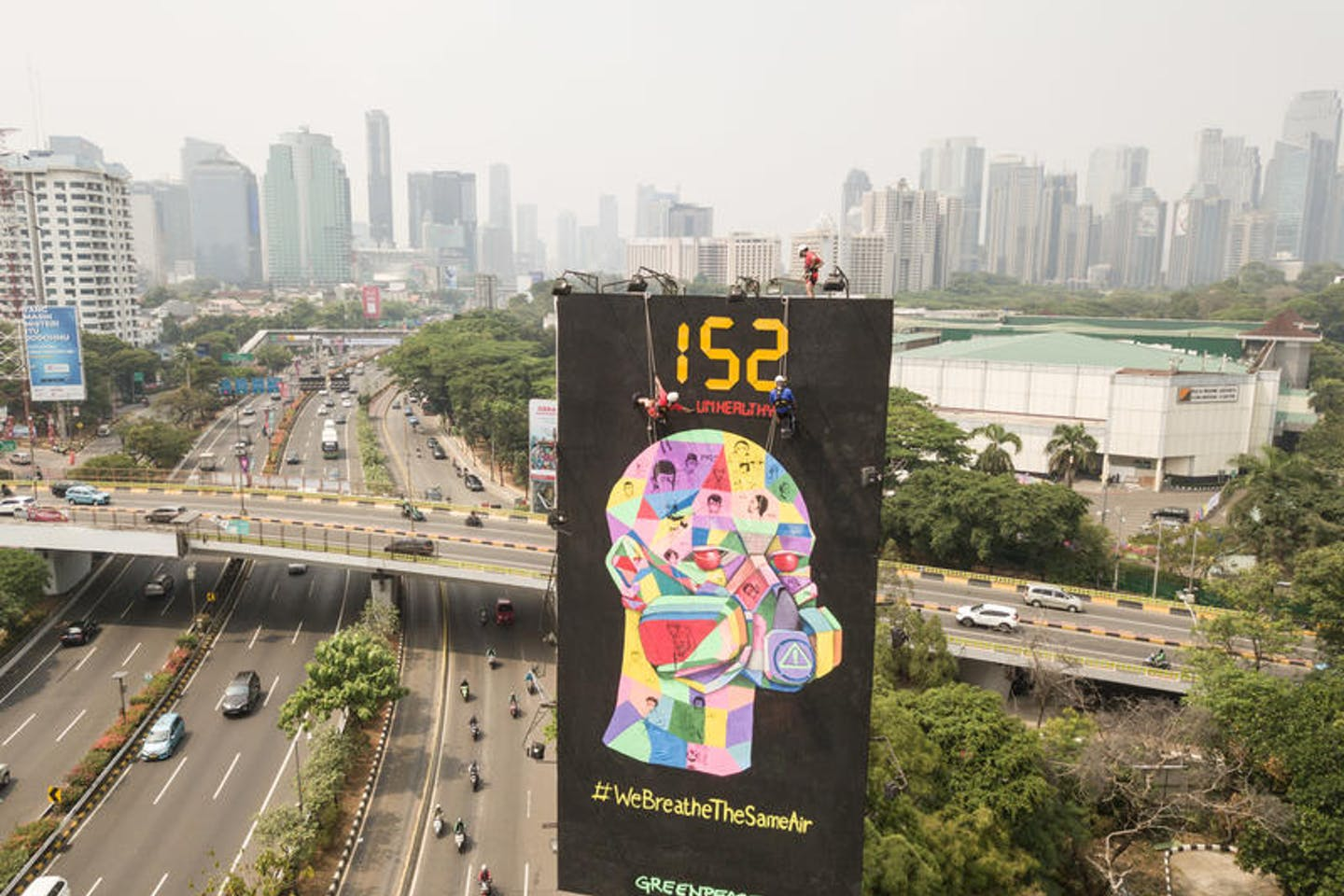 Greenpeace activists hang clean air campaign billboard in