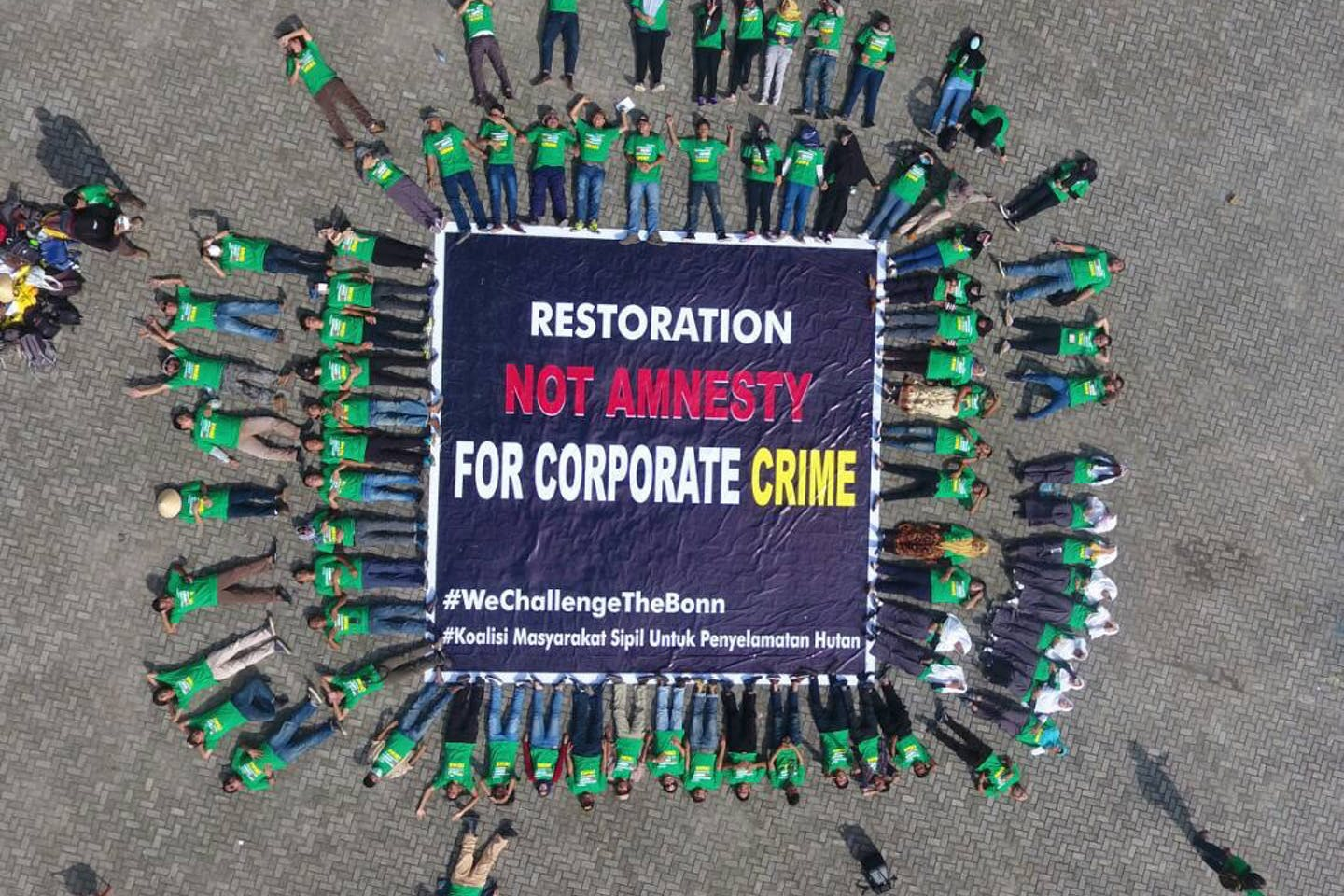 """Protester lie outside the Asian launch of the Bonn Challenge, calling on the organisation not to be used to mask the """"corporate crime' of pulp and paper companies that are threatening the environmental and livelihoods in South Sumatra: Image: Hutan Kita Institute"""