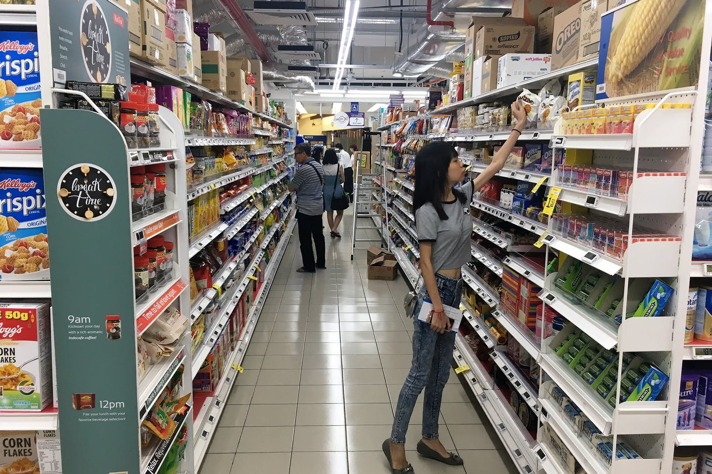 Choosing the responsible food option? A customer a supermarket in Singapore reaches for an item. Image: Eco-Business