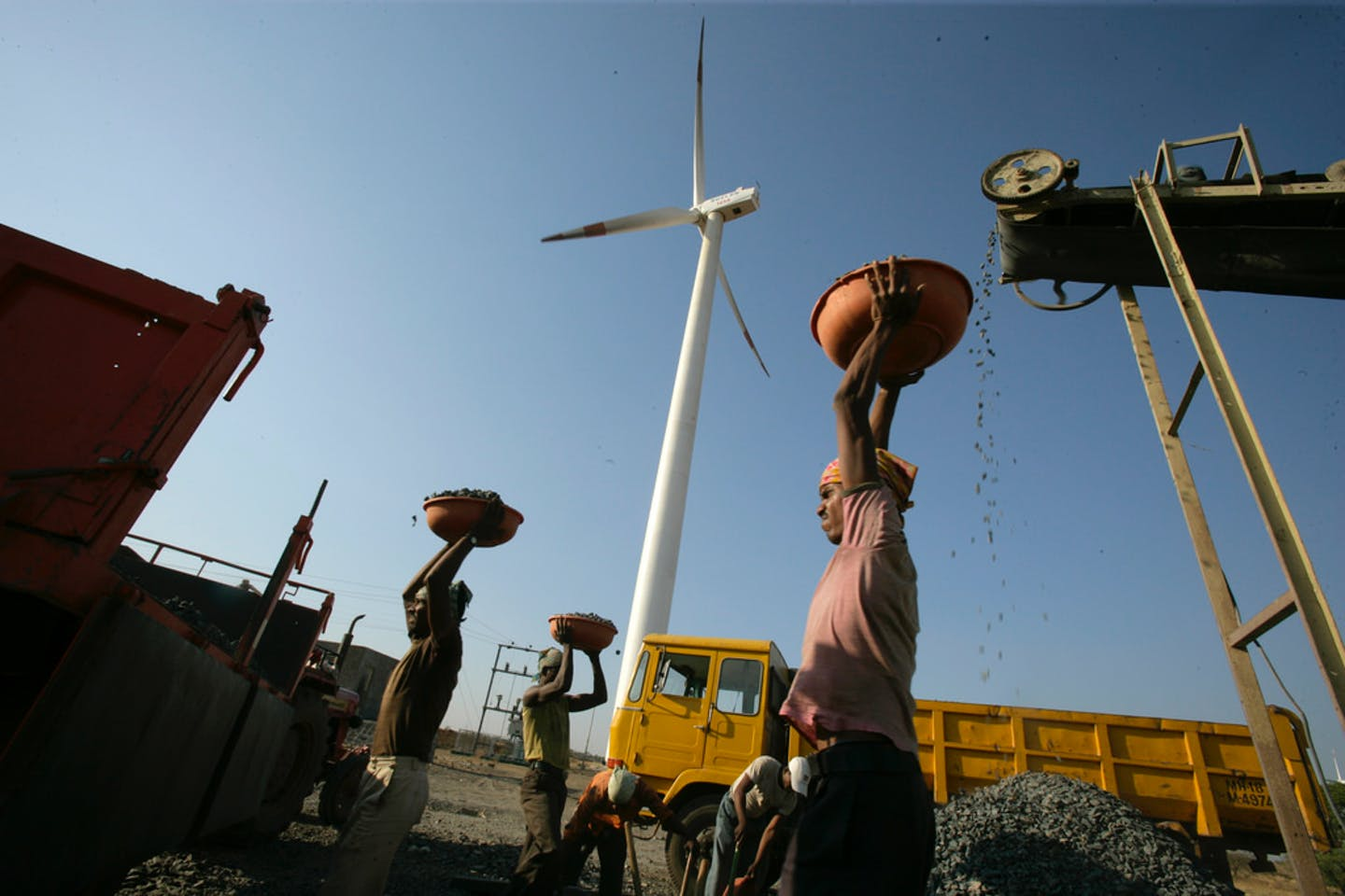 A laborer hauls crushed rocks pulversied by a diesel-powered crusher in the shadow of a wind turbine.