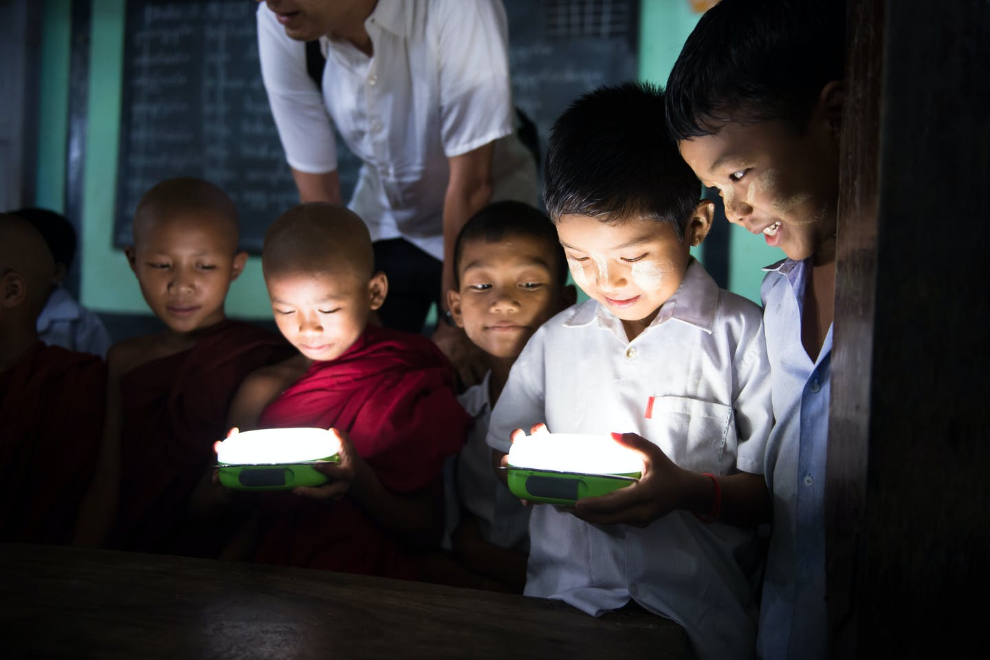 Children in Myanmar hold a solar lamp provided by Panasonic