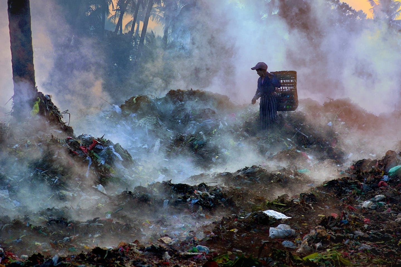 A girl sifts through trash in Nyaung U, Myanmar