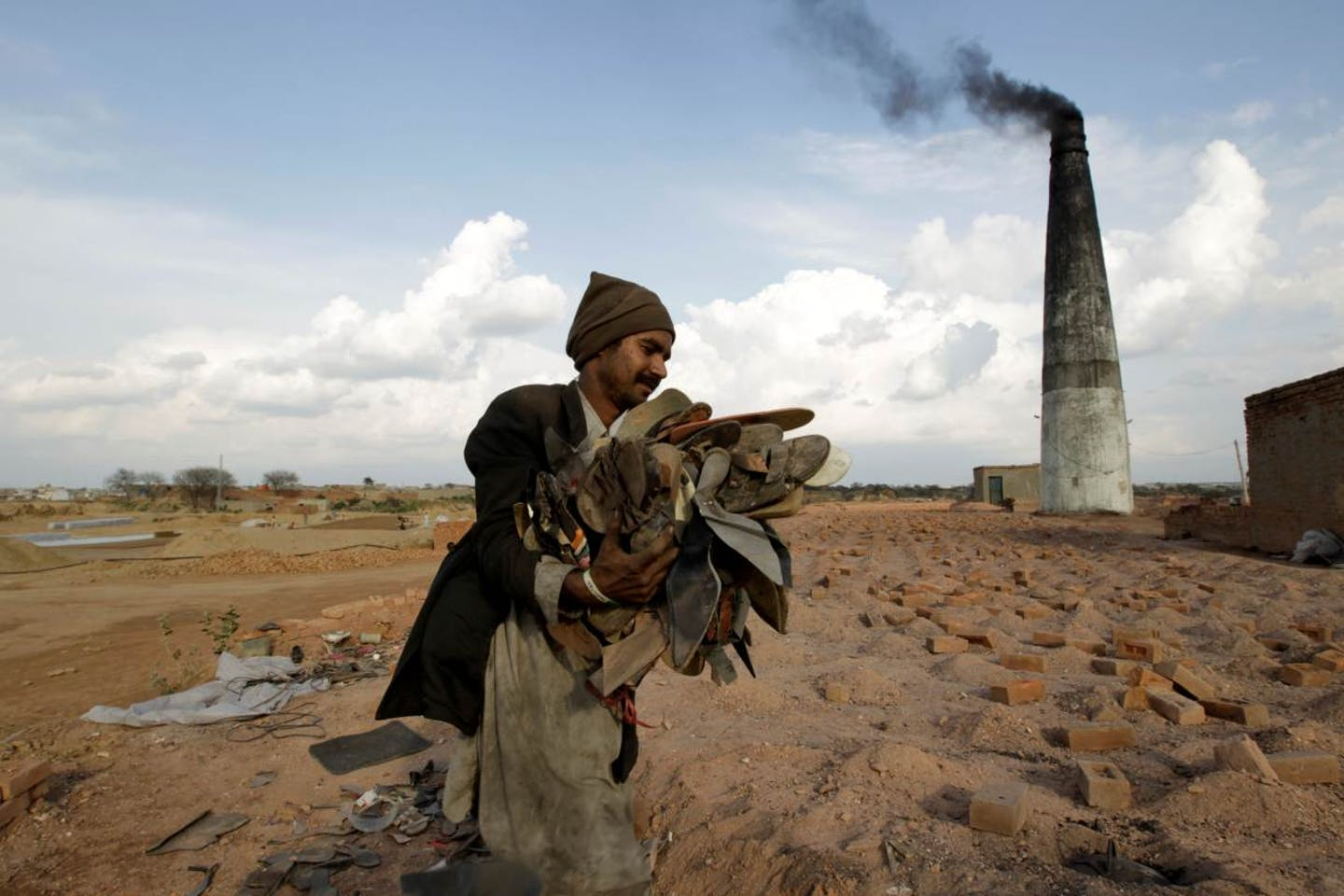 worker burns slipper at brick kiln factory in Pakistan