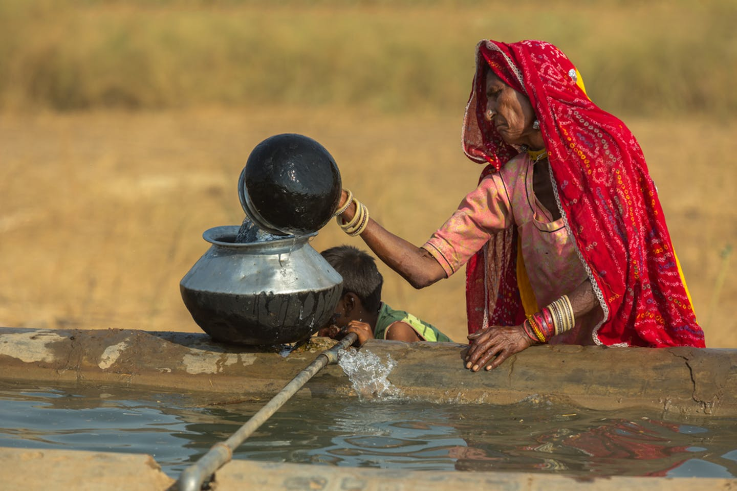 A woman fills her container with water in India.