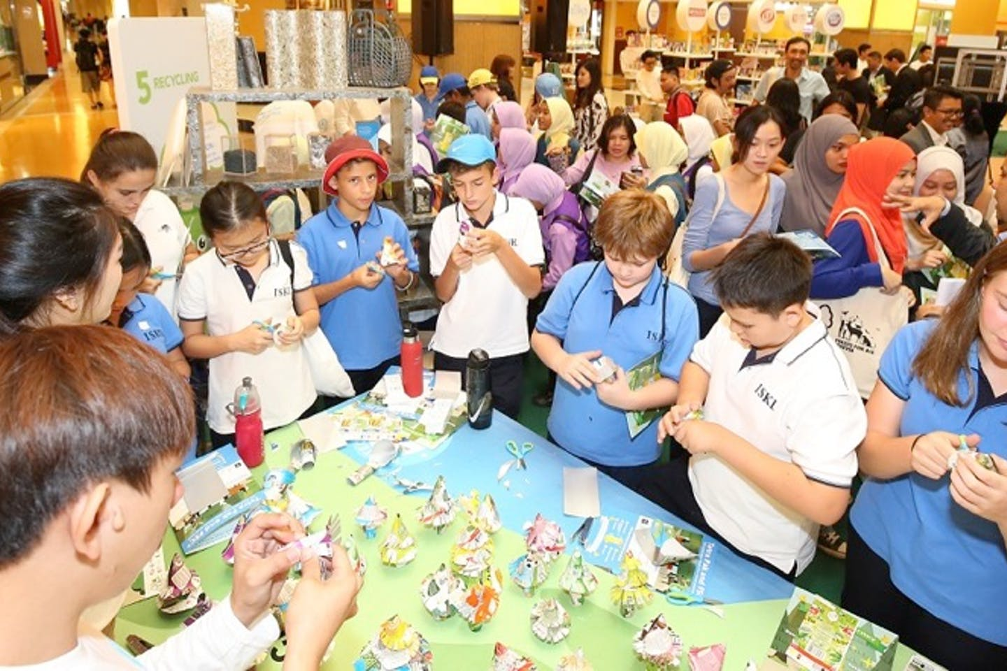 Students from the International School of Kuala Lumpur learning how to turn used cartons into decorative trees at Sunway Pyramid on 11 November 2016.