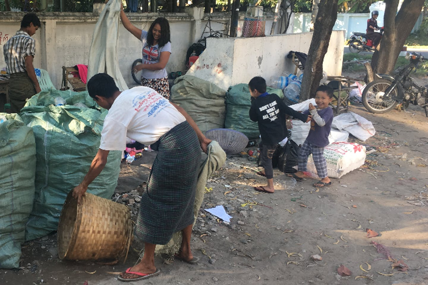 Children play with informal waste pickers in Myanmar